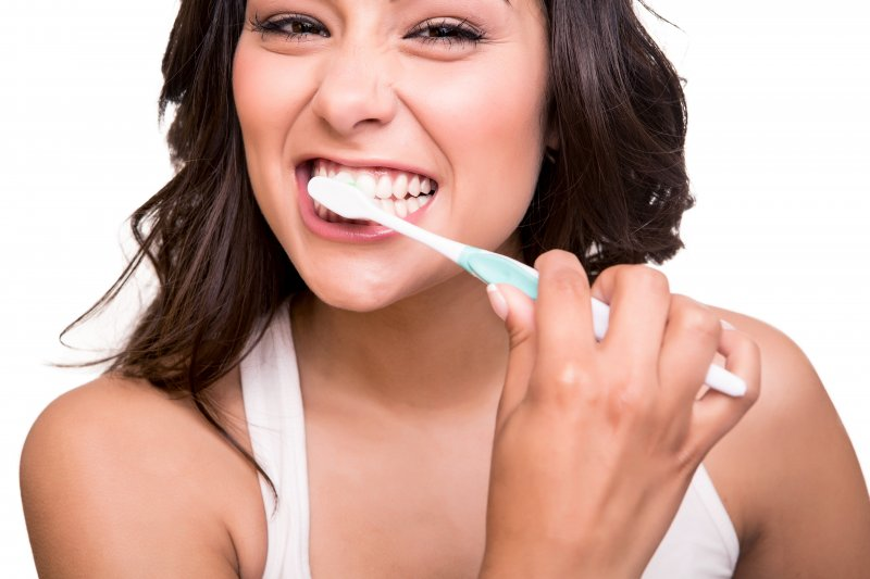 woman brushing her teeth before visiting dentist in Mount Vernon